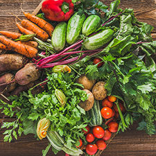 Fresh organic vegetables harvest. Local farmer market with vegetable box on wooden background, vegetarian food concept